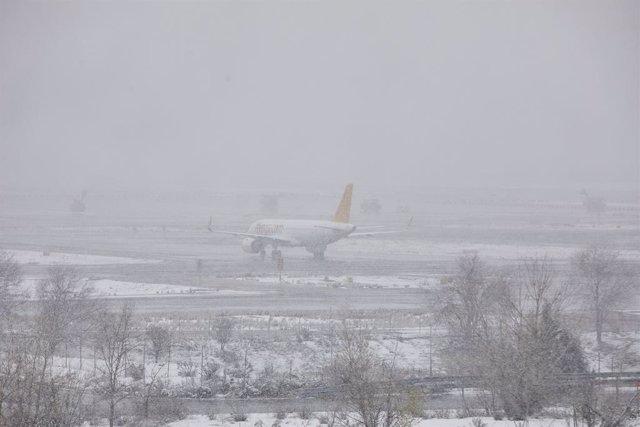 Un avión de la compañía Flypgs en el Aeropuerto de Madrid-Barajas Adolfo Suárez, en Madrid (España), a 8 de enero de 2021. El temporal de nieve y las heladas han obligado al aeropuerto a descongelar más de 60 aviones esta mañana. Aena ha activado el Plan