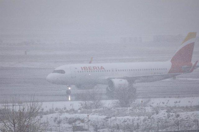 Un avión de la compañía Iberia en el Aeropuerto de Madrid-Barajas Adolfo Suárez, en Madrid (España), a 8 de enero de 2021. El temporal de nieve y las heladas han obligado al aeropuerto a descongelar más de 60 aviones esta mañana. Aena ha activado el Plan
