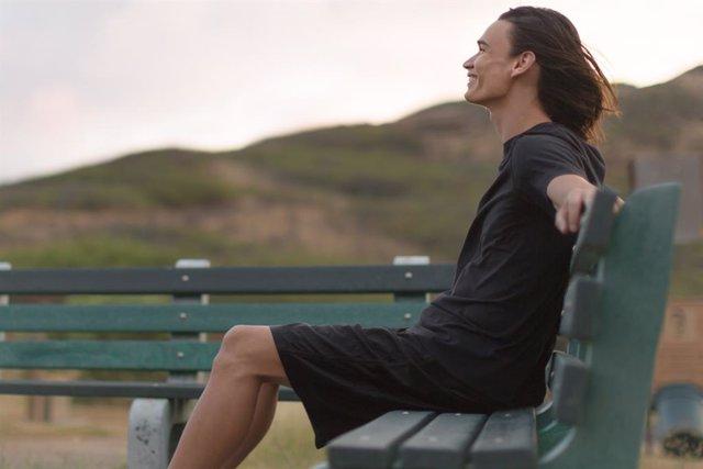 Joven sentado feliz en un banco.