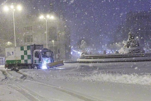 Una máquina quitanieves pasa junto a la fuente de Cibeles, cubierta de nieve por la borrasca Filomena, en Madrid (España) a 9 de enero de 2021.