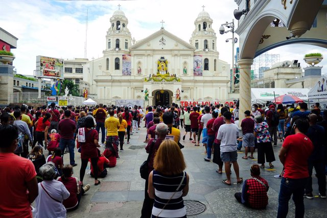 09 January 2021, Philippines, Manila: Hundreds of devotee take part in a mass outside the Minor Basilica of the Black Nazarene. People attend the mass in batches instead of parading with the Black Jesus of Nazarene due to the coronavirus pandemic. Photo: