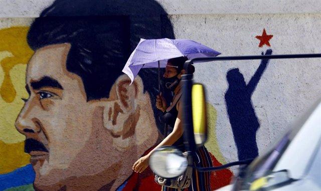 Una mujer camina bajo su paraguas frente a un mural con la imagen del presidente de Venezuela, Nicolás Maduro, en la ciudad de Guacara