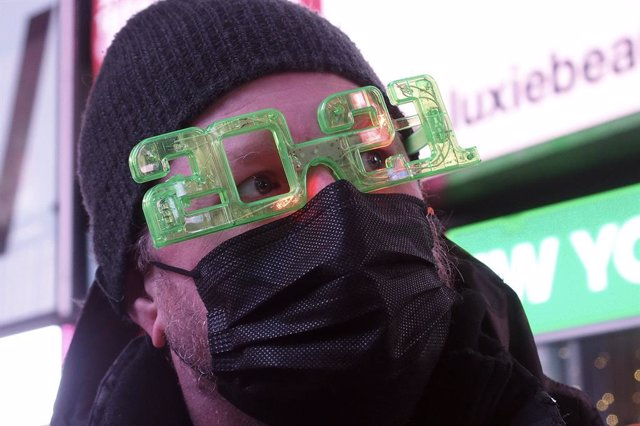 31 December 2020, US, New York: A man wears a face mask as he walks near the closed-off Times Square after celebrations have been truncated this New Year's Eve due to the ongoing coronavirus pandemic. Photo: Debra L. Rothenberg/ZUMA Wire/dpa