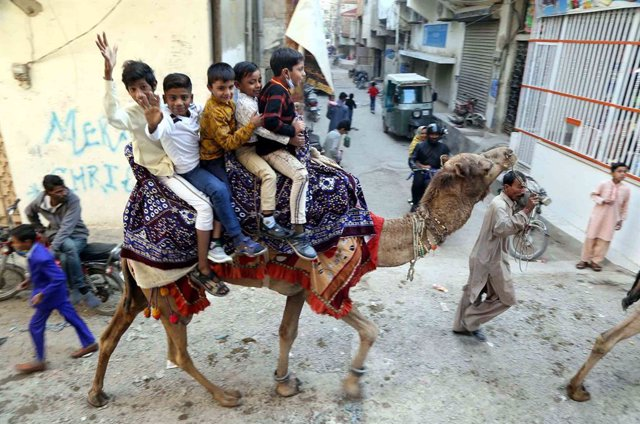 25 December 2020, Pakistan, Karatschi: Children from the Christian community ride a camel in Mehmoodabad district on Christmas Day. Photo: Ppi aju/PPI via ZUMA Wire/dpa