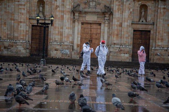 Un grupo de personas camina por una vacía plaza de Bolívar en Bogotá en el segundo día de cuarentena estricta.