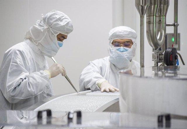 06 January 2021, China, Beijing: Scientists work on the production line of Sinovac Biotech's coronavirus (COVID-19)vaccine. Photo: -/TPG via ZUMA Press/dpa