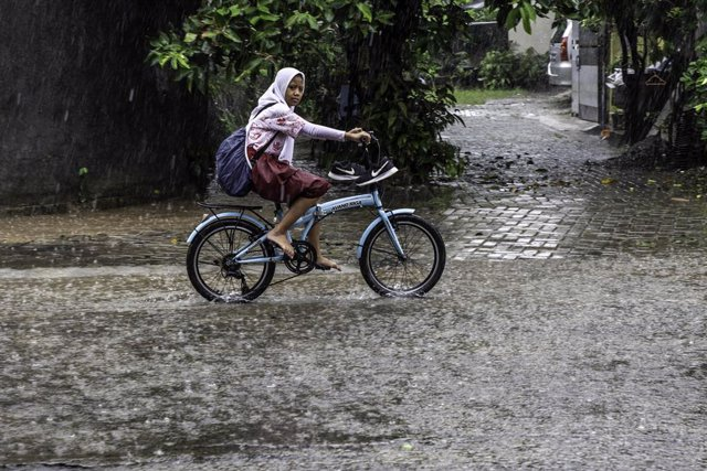 22 January 2019, Indonesia, South Tangerang: A girl rides a bicycle during a heavy rain. Photo: Donal Husni/ZUMA Wire/dpa