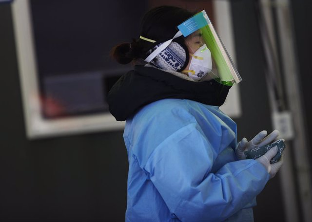 10 January 2021, South Korea, Seoul: A medical worker warms her hands with instant hot packs at a makeshift clinic for coronavirus testing in front of Seoul Station amid a cold wave sweeping the country. Photo: -/YNA/dpa