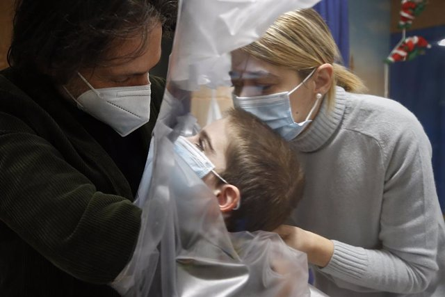 29 December 2020, Italy, Rome: A hospitalized child embraces his parents through a transparent sheet used to prevent the transmission of the COVID-19 at the Department of paediatric rehabilitation and developmental disabilities of IRCCS at the San Raffael