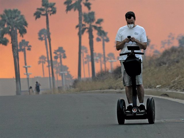 A man usues his cell phone while riding a Segway November 15, 2008 as the glow from a fire is seen in the distance in Yorba Linda, California.