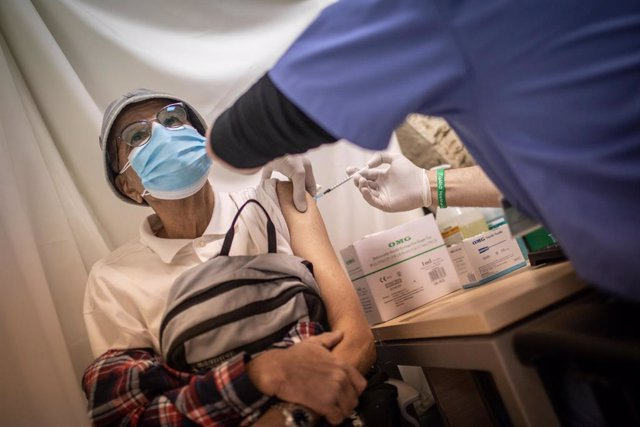 04 January 2021, Israel, Jerusalem: A citizen receives a Coronavirus (COVID-19) vaccine from medical personnel at a vaccination center in Jerusalem. Israel has vaccinated 1 million people, two weeks after the launch of its Covid-19 inoculation campaign. P