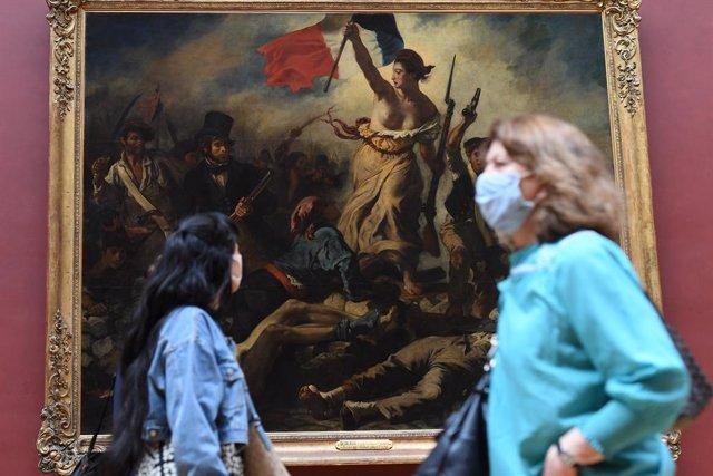 Una mujer con mascarilla frente al cuadro 'La libertad guiando al pueblo' de Eugène Delacroix, en el Museo del Louvre de París
