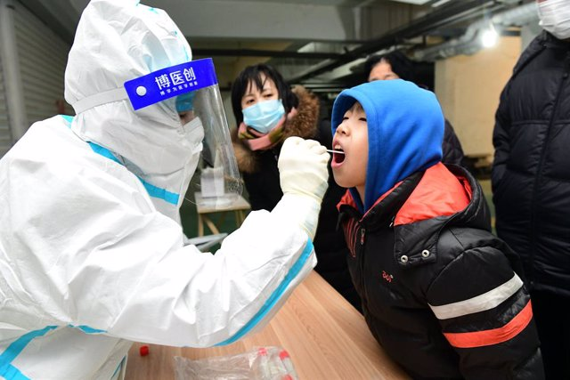 06 January 2021, China, Shijiazhuang: A health worker takes a swab from a child for coronavirus (COVID-19) test. Photo: -/TPG via ZUMA Press/dpa