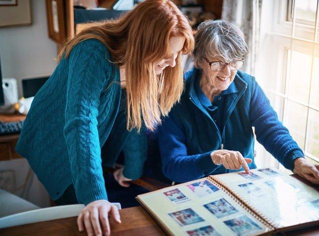 Dos mujeres mirando un albúm de fotos.-