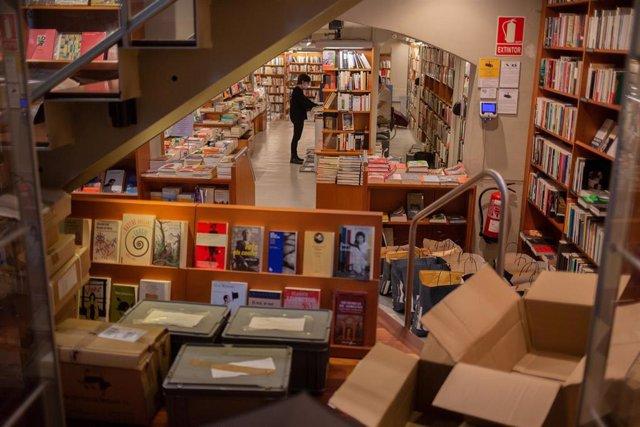 Trabajadores de la librería Laie Pau Claris colocan libros y material en las estanterías del local que permanece cerrado al público por la crisis del Covid-19. En Barcelona, Cataluña, (España), a 22 de abril de 2020.
