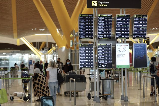 Pasajeros junto a páneles de información en la Terminal T4 del aeropuerto Adolfo Suárez Madrid-Barajas, en Madrid (España), a 11 de septiembre de 2020. Los aeropuertos de la red de Aena, el Adolfo Suárez Madrid-Barajas entre ellos, cerraron agosto con uno