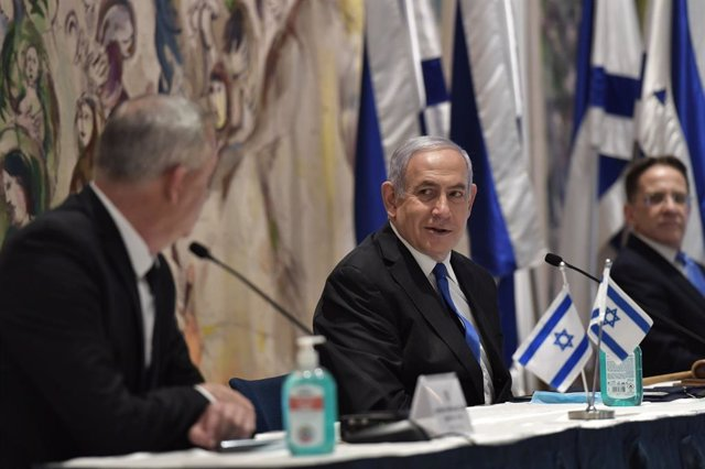 HANDOUT - 17 May 2020, Israel, Jerusalem: Israeli Prime Minister Benjamin Netanyahu (C) and Alternate Prime Minister Benny Gantz (L) attend the first government meeting of the 35th Israeli government. Netanyahu has been sworn in as Israel's new prime mini