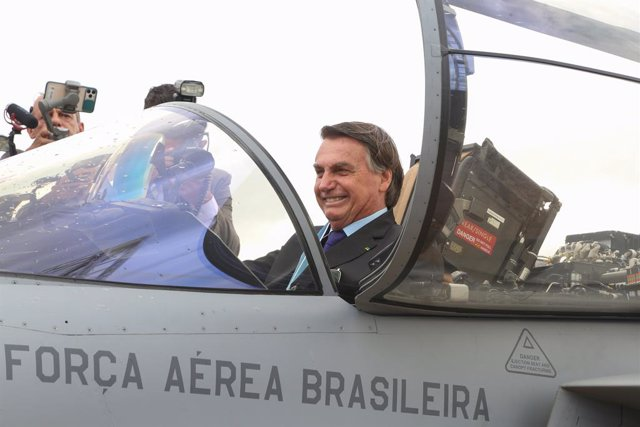 HANDOUT - 23 October 2020, Brazil, Brasilia: Brazilian President Jair Bolsonaro (R) sits inside the cockpit of a Swedish-made Saab JAS 39 Gripen jet fighter during a ceremony held on the Brazilian Aviator's Day. The aircraft is one of 36 Gripen jets bough