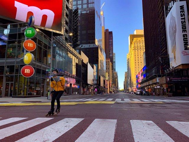 Un hombre con mascarilla patinando en Nueva York durante la pandemia de coronavirus