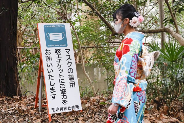 11 January 2021, Japan, Tokyo: A Japanese girl dressed in colorful kimono walks past a signboard saying 'Please wear a mask' at the Meiji Shrine during the Coming of Age Day holiday. The Coming of Age Day (Seijin-no-Hi) is a holiday to congratulate and en