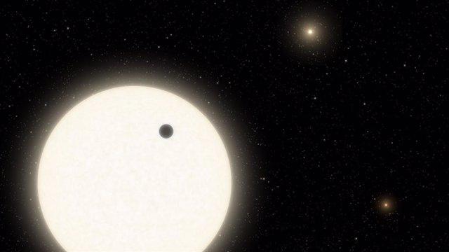 Esta ilustración muestra el planeta KOI-5Ab en tránsito por la cara de una estrella similar al Sol, que es parte de un sistema de estrellas triples ubicado a 1.800 años luz de distancia en la constelación de Cygnus
