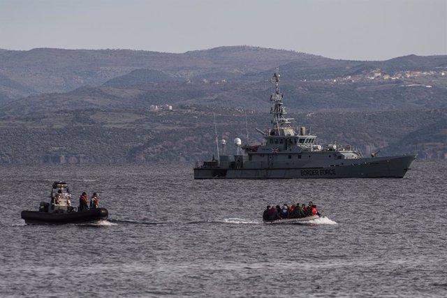 Una embarcación con migrantes llega a la isla griega de Lesbos, frente al barco británico 'HMC Valiant', parte de la misión Frontex