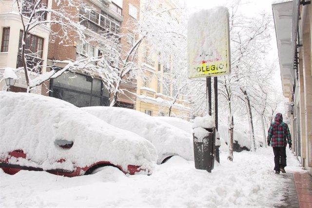 Una persona pasea por una céntrica calle cubierta de nieve junto al acceso de un colegio en Madrid