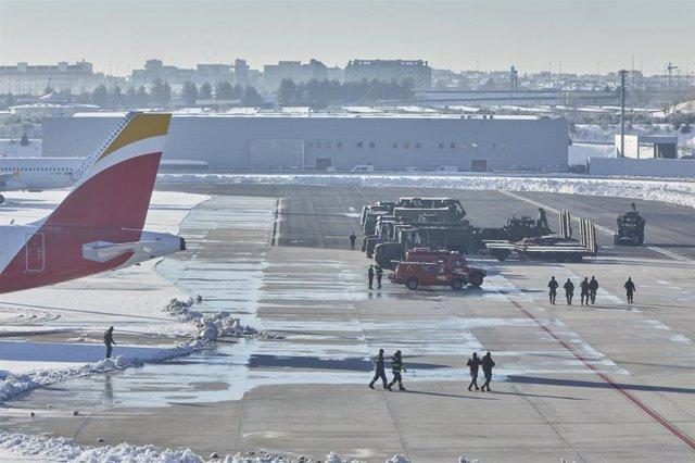 Varios militares de la Unidad Militar de Emergencia (UME) caminan por la pista del aeropuerto Madrid-Barajas Adolfo Suárez, en Madrid (España), a 12 de enero de 2021