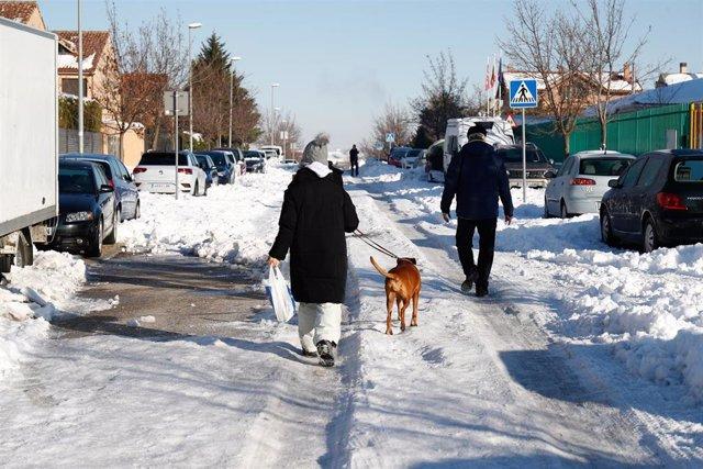 Varias personas caminan por una de las carreteras llenas de nieve y hielo tras el paso de la borrasca 'Filomena', en Valdemoro, Madrid (España), a 12 de enero de 2021. El dispositivo de limpieza de nieve en calles puesto en marcha por el Ayuntamiento y el