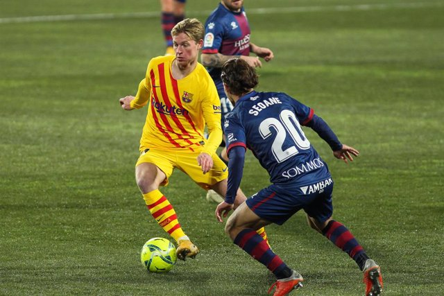Frenkie de Jong of FC Barcelona and Jaime Seoane of SD Huesca in action during La Liga football match played between SD Huesca and FC Barcelona at El Alcoraz stadium on January 03, 2021 in Huesca, Spain.