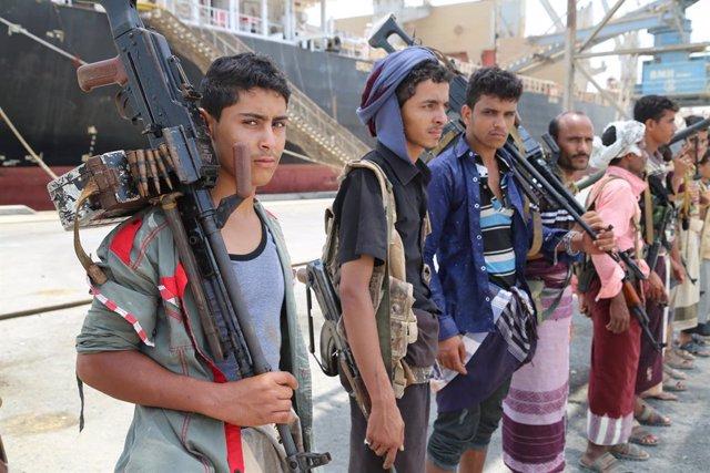 Combatientes huthis durante su retirada del puerto de Salif, en Hodeida