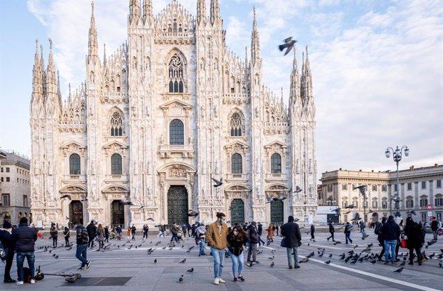 Personas con mascarillas ante la catedral de Milán