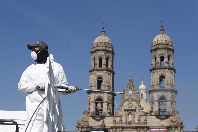 Un trabajador sanitario desinfecta una zona cercana a la Basílica de nuestra señora de Zapopan, en México, en plena pandemia del coronavirus.