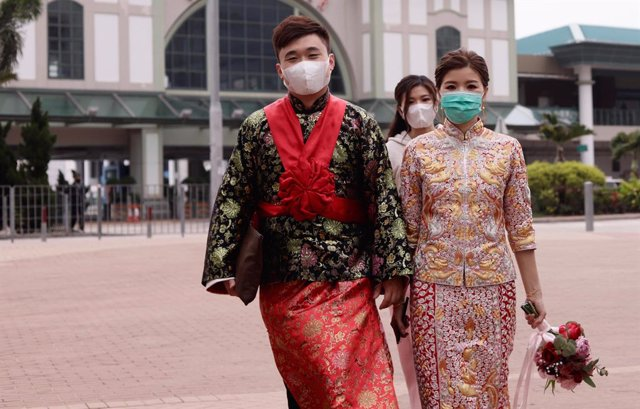 29 March 2020, China, Hong Kong: A bride and a groom dressed in traditional Chinese wedding costumes protect themselves with face masks amid the coronavirus pandemic. Photo: Liau Chung-Ren/ZUMA Wire/dpa