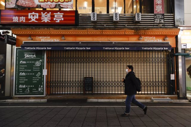 10 January 2021, Japan, Tokyo: A man wears a face mask leaves Kabukicho (the red-light district of Tokyo) after the establishments closed at 8 pm to stop the COVID-19 infections in the capital. Photo: Rodrigo Reyes Marin/ZUMA Wire/dpa