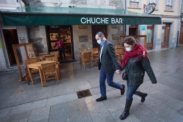 Dos personas pasan frente a una terraza en en Lugo, tras el levantamiento del cierre perimetral de la ciudad, en Lugo, Galicia (España), a 30 de diciembre de 2020.  Lugo y Ourense serán las dos únicas urbes gallegas sin cierre perimetral en Fin de Año, de