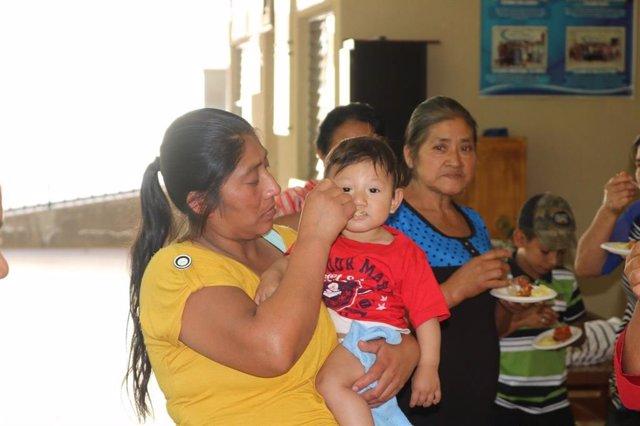 Una madre y su hijo participan en un proyecto de nutrición de Paz y Bien, en colaboración con la Diputación de Huelva.