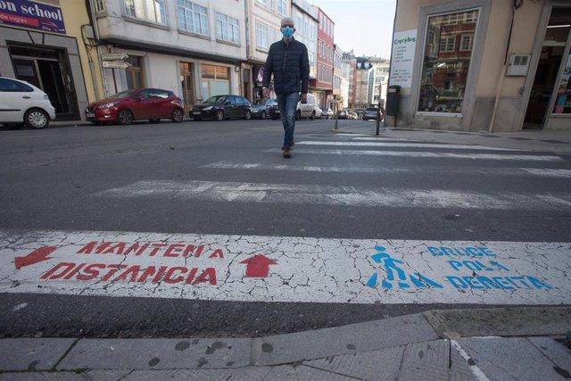 Una persona cruza un paso de cebra el mismo día de la entrada en vigor de nuevas restricciones impuestas por la crisis del Covid-19 en el municipio de Vilalba, Lugo, (España), a 21 de noviembre de 2020. Entre las medidas, además del cierre perimetral, se