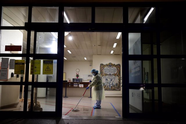 08 January 2021, Portugal, Lisbon: A cleaning worker wearing a protective suit cleans the floor at the Curry Cabral Hospital in Lisbon. Portugal reported a record 10,176 new Coronavirus (COVID-19) cases and 118 deaths in 24 hours, the highest daily figure