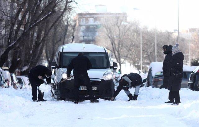 Vecinos del barrio de Pueblo Nuevo ayudan a un conductor a sacar su coche de la nieve, en Madrid (España), a 13 de enero de 2021.   Madrid sigue cubierto de nieve cinco días después de la gran nevada provocada por el paso de la borrasca 'Filomena'. El Ayu