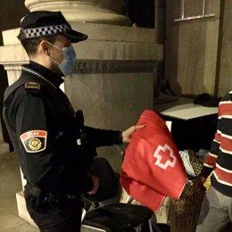 Un agent de la Policia Local de València atén a una persona sense llar (arxiu)