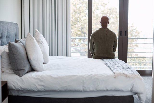 Hombre sentado en la cama. Depresión, Catatonia.