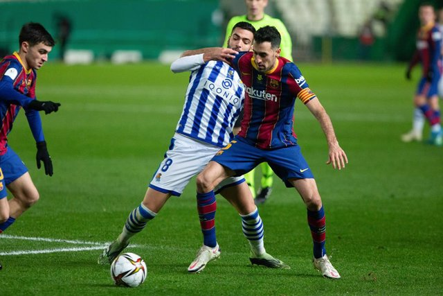 Mikel Merino of Real Sociedad and Sergio Busquet of Barcelona during the Spanish SuperCup First Semifinal between Real Sociedad and Futbol Club Barcelona at Nuevo Arcangel stadium on January 13, 2021 in Cordoba, Spain.