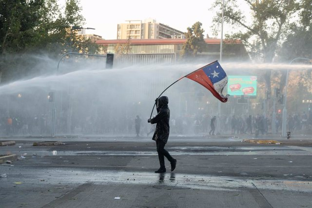 08 January 2021, Chile, Santiago: A man waves the Chilean flag in front of the water cannons of the police car during a protest against the police and the government of the Chilean President Sebastian Pinera. Photo: Matias Basualdo/ZUMA Wire/dpa