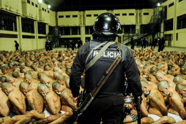 Un policía frente a decenas de presos tras la declaración de emergencia del presidente, Nayib Bukele, de las cárceles de El Salvador.