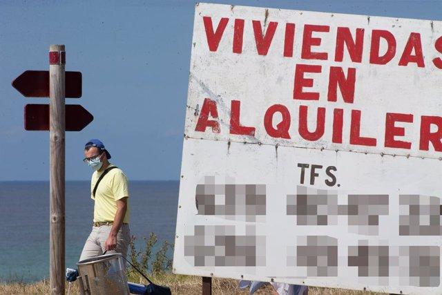 Un home camina al costat d'un cartell d'habitatges de lloguer. A Mariña, Galícia (Espanya), 26 de juliol del 2020.