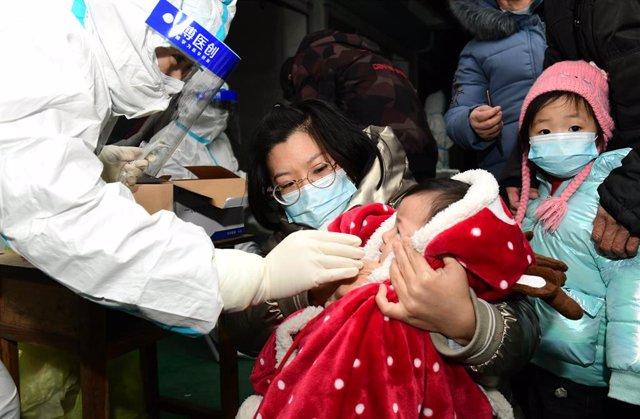 06 January 2021, China, Shijiazhuang: A health worker takes a swab from a child for coronavirus (COVID-19) test. Photo: -/TPG via ZUMA Press/dpa