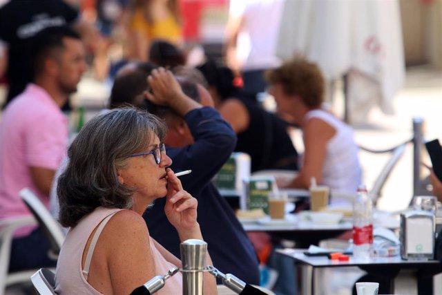 Personas fumando en terrazas y vías públicas  durante el día en el que se ha decretado la prohibición de fumar en espacios públicos si no se respeta la distancia de seguridad establecida. Málaga a 14 de agosto del 2020