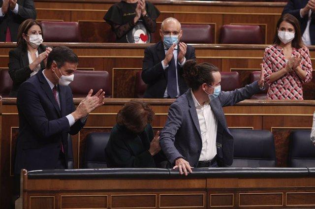 El presidente del Gobierno, Pedro Sánchez (i), acompañado de otros miembros del partido aplauden al vicepresidente segundo del Gobierno, Pablo Iglesias (c), tras su intervención en la segunda sesión del pleno en el que se debate la moción de censura plant
