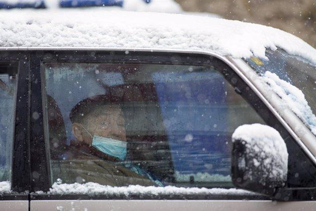 Un anciano con mascarilla permanece en su vehículo durante la nevada en Becerrea, en Lugo, Galicia (España), a 4 de diciembre de 2020.